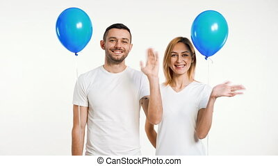 Smiling man and woman with hands raised in greeting and ...