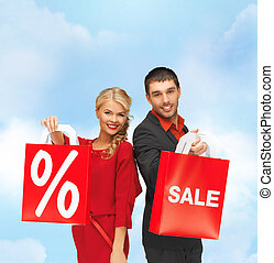smiling man and woman with shopping bag - sale and shopping...