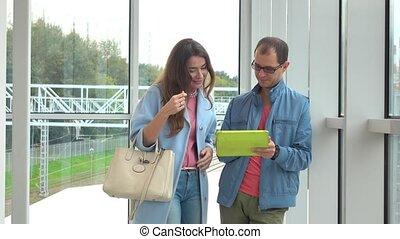 Smiling man and young woman using tablet computer at modern railroad station. 4K shot