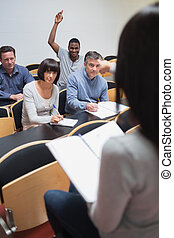 Smiling man asking question in lecture in college