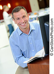 Smiling man at computer holding book