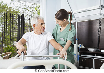 Smiling Man Being Assisted By Female Nurse In Using Walker
