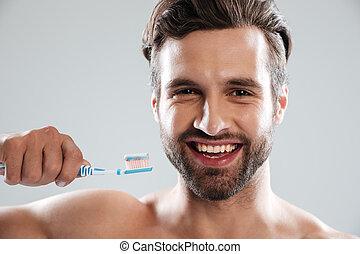 Smiling man brushing teeth
