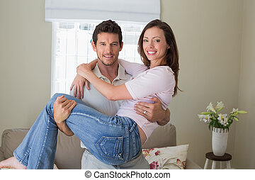 Smiling man carrying woman at home