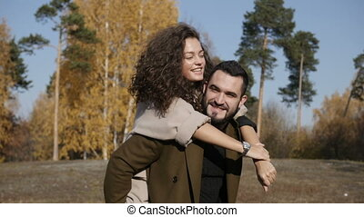 Smiling man carrying woman on back