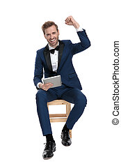 smiling man celebrating success while sitting with notepad in hand