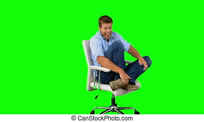 Smiling man cheeringand turning on swivel chair on green screen in slow motion