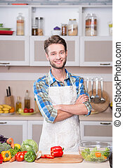 Smiling man cooking dinner in kitchen