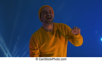 Smiling man dancing in studio. Joyful guy gesturing with hands. Man having fun. man smiling and dancing challenge dance in good mood on blue background.Unstoppable fun, happiness, comical portrait.
