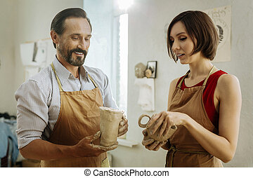 Dark-haired man smiling while watching his woman working