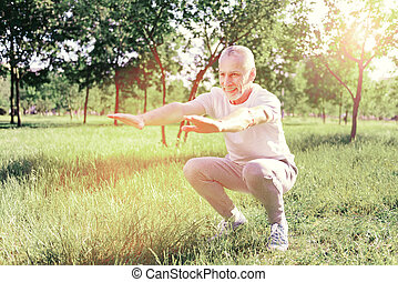 Smiling man doing exercises outdoors