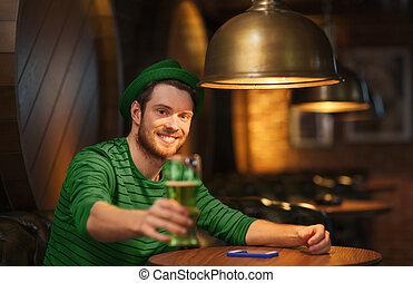 smiling man drinking green beer at bar or pub