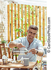 Smiling man drinking tea in a summer cafe.