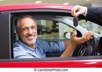 Smiling man driving a car while salesman his giving key