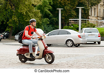 Smiling man driving through city on a motorcycle