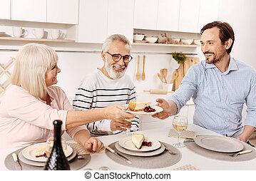 Smiling man enjoying family dinner at home