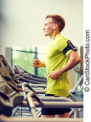 smiling man exercising on treadmill in gym - sport, fitness...