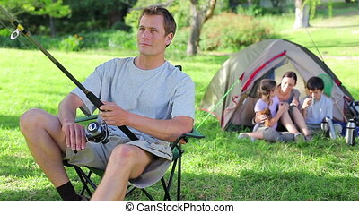 Smiling man fishing in front of his family