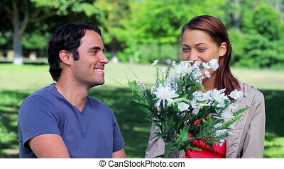 Smiling man giving a bunch of flowers to his girlfriend