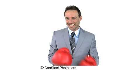Smiling man giving punches with boxing gloves in front of...