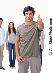 Smiling man giving thumb up with friends behind him