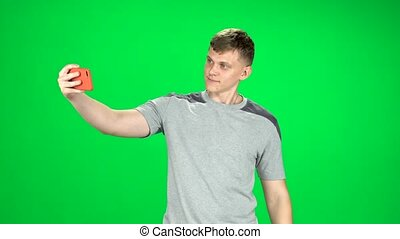 Smiling man goes and takes a selfie with smartphone on green screen at studio.
