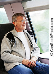 smiling man goes in a train and looks out of the window