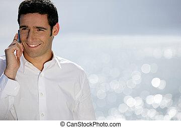 Smiling man having phone conversation