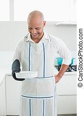 Smiling man holding a baking dish in kitchen