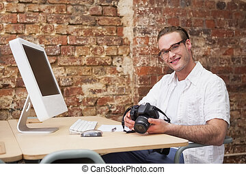 Smiling man holding a camera