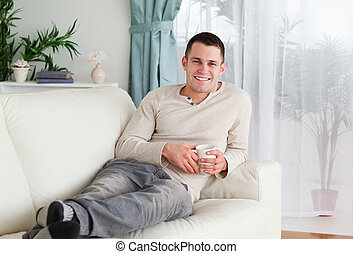 Smiling man holding a cup of coffee