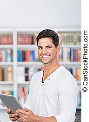 Smiling man holding a tablet in front of bookshelf