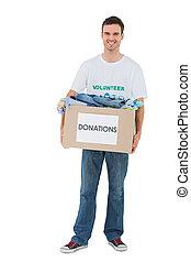 Smiling man holding donation box