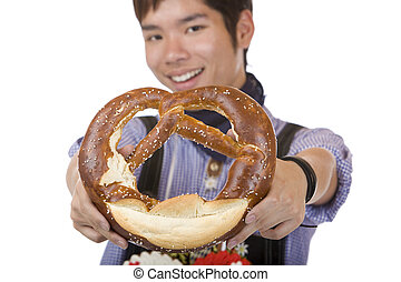 Smiling man holding Oktoberfest Pretzel in hands - Asian...