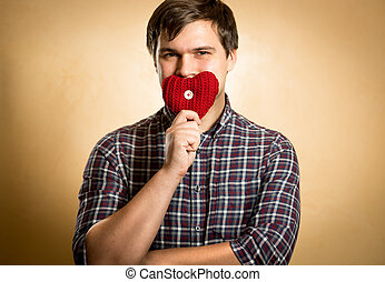 smiling man holding red heart at mouth