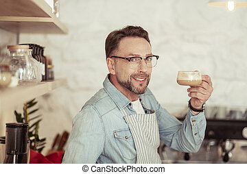 Smiling man holding up his cup of coffee.