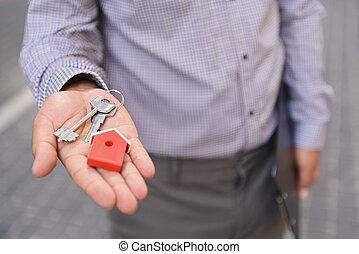 Smiling man holding up keys