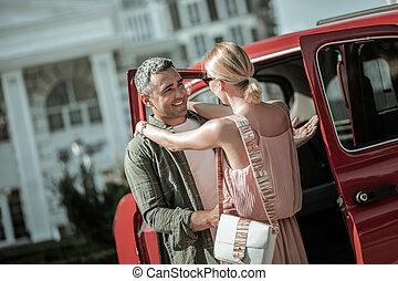 Smiling man hugging his wife before leaving.