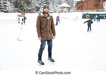 Smiling man ice skating outdoors