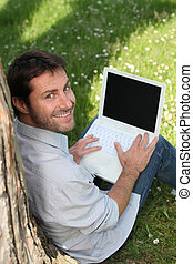 Smiling man in a park, using a laptop with the screen left ...