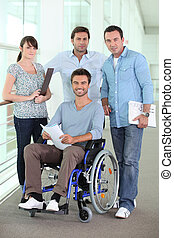 Smiling man in a wheelchair with colleagues