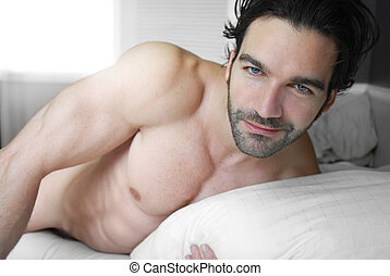 Smiling man in bed - Happy playful young man shirtless in...