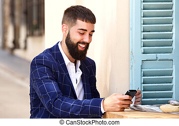 Smiling man in business suit sitting with mobile phone