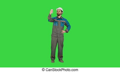 Smiling man in helmet make selfie on a Green Screen, Chroma Key.