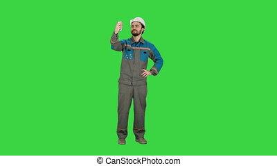 Smiling man in helmet make selfie on a Green Screen, Chroma Key.