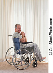 Smiling man in his wheelchair at ho