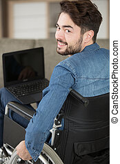 smiling man in his wheelchair at home