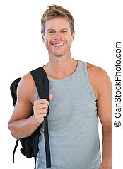 Smiling man in sportswear holding backpack