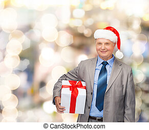 smiling man in suit and santa helper hat with gift -...