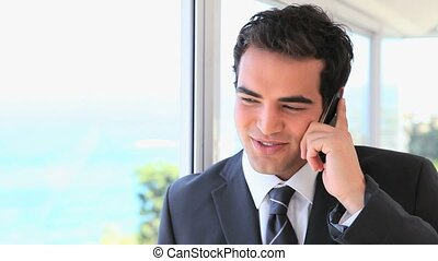 Smiling man in suit on the phone next to a window